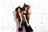 portrait two happy young women in black witch halloween costumes on party over white background. firecrackers in the background. confetti . the concept of Halloween . funny faces