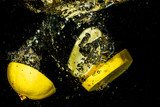 Yellow lemon slices splashing into water.
