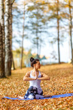 Young woman doing yoga exercises in the autumn city park. Health lifestyle concept.
