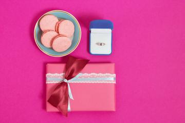 Macarons with ring on a pink background . An offer of marriage. Top view, toned image, film effect