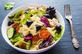 Pasta salad made from farfalle, red onion, cherry tomatoes, fresh cucumbers, black olives, mix of green salad leaves. White bowl on black stone background.