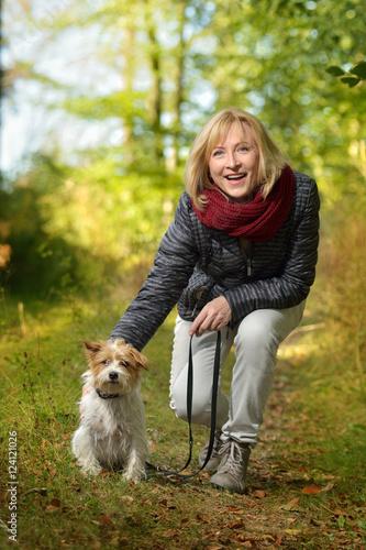 Poster Attraktive reifere Frau mit Terrier im Wald