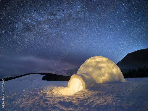 Zimowy nocny krajobraz ze śniegiem igloo i gwiaździste niebo