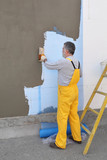 House renovation, polystyrene wall insulation, worker spreading mortar, use trowel