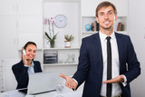 positive young man executive manager standing in office