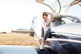 Woman in sunglasses sitting in small private plane - 124146626