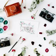 Wohnung lag. Künstler-Arbeitsbereich mit Vintage-Retro-Foto-Kamera, und Aquarell gemalt Kamera, rote Rosen und Eukalyptus. Draufsicht Anordnung