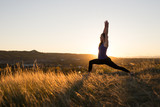 Woman doing yoga warrior I pose during sunset