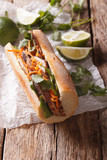 Traditional Vietnamese Banh Mi sandwich with pork, cilantro, carrot close-up. vertical