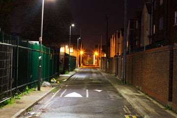 Looking down a dark empty back alleyway at night © sas