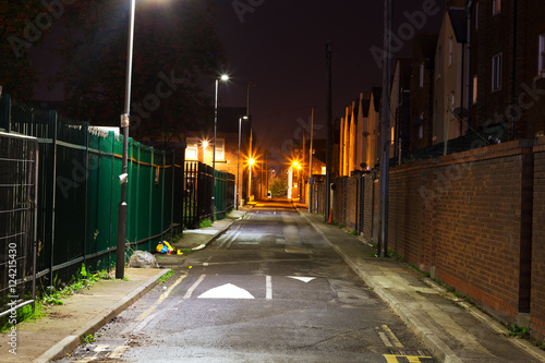 Looking down a dark empty back alleyway at night