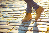 Warm yellow boots. Walking in autumn leaves - 124216289