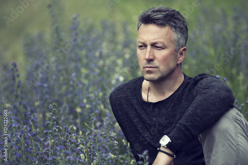 Portrait of handsome mid-adult man posing on summer meadow, imag Poster
