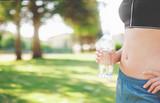Bottiglietta di acqua in mano di atleta con pancia piatta o sportiva