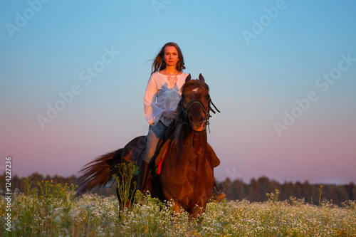 Portrait of beautiful woman riding horse at sunset Poster
