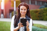 Young woman listening music by headphones outdoor