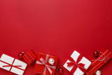 Christmas gifts presents on red background. Simple, classic red and white wrapped gift boxes with ribbon bows and festive holiday decorations. Horizontal bottom border. - 124304483