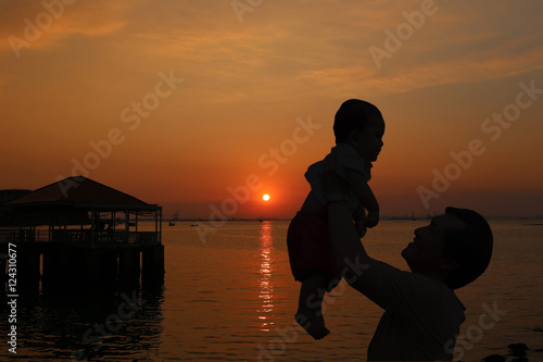 Father were holding a baby to holds up and sunset view on evenin Poster