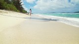 Young woman walking in white dress on a tropical beach at Seychelles