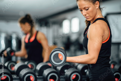 Exercising in gym. Attractive female athlete exercising with dumbbells