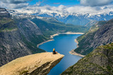 Amazing view with Trolltunga and a girl sitting on it. Norway - 124379846
