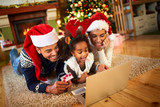 Smiling family lying on floor front of Christmas tree