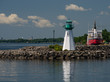 White and green Harbour lighthouse with a coast guard ship in the background