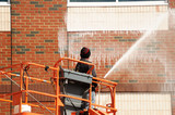 outdoor worker cleaning the exterior wall of building through pressure water - 124407290