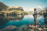 Fototapety Man Fisherman fishing with rod lake and mountains on background Lifestyle Travel hobby concept active summer vacations