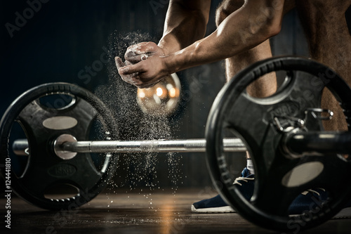 Fridge magnet Sports background. Young athlete getting ready for weight lifting training. Powerlifter hand in talc preparing to bench press