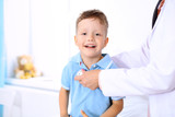 Happy little boy having fun while is being examine by doctor by stethoscope. Health care, insurance and help concept