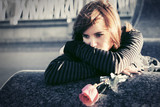 Sad young woman with a red rose on city street