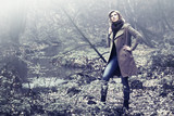 Happy blond fashion woman in classic coat walking outdoor