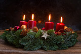 Evergreen fir tree advent garland with four red burning candles on wooden table