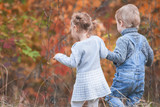 Happy children outdoor at fall season, holding hands. Has date