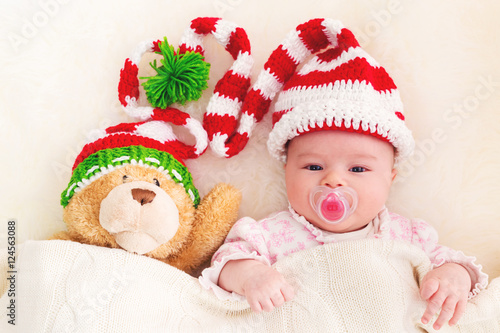 66df701c9da Baby girl in a Christmas hat with her teddy bear Poster ID F124563088