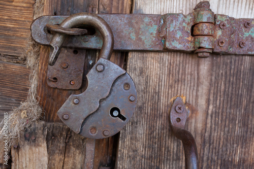 Poster Old rusty padlock and latch on a wooden door with rusty nails