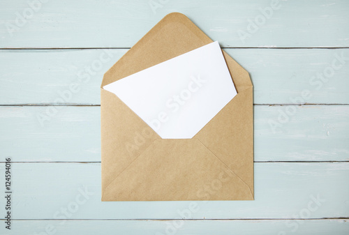 An open brown envelope with letter on a blue wooden desk top background