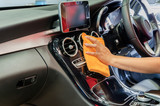 Hand with microfiber cloth cleaning interior car