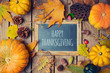 Thanksgiving background with chalkboard. Autumn pumpkin and fall leaves on wooden table. View from above
