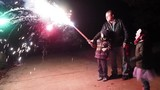 Family playing with fireworks at night