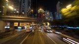 Night Hong Kong view with high-rise buildings, road intersection and transport driving on the highway with rails. Shot in motion