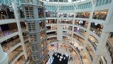 View of shopping mall interior. Multistorey trade centre with customers
