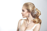 Beauty portrait of a cute blonde gorgeous bride with a beautiful hairstyle in jewelry.