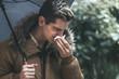 terrified man with handkerchief sneezing, flu