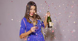 Sexy young woman celebrating New Year with a bottle and flute of chilled champagne as she dancing amidst falling confetti and colorful streamers
