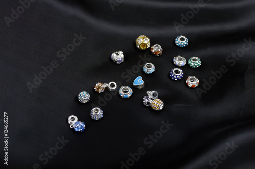 Poster Beads, charms and pendants scattered on black satin
