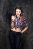 Girl show ok sign in checkered shirt and jeans