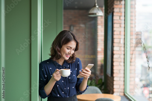 Beautiful cute asian young businesswoman in the cafe, using mobi