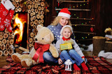 Mother and son in caps of Santa Claus on a background  the cozy fireplace